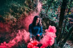 Woman Wearing Blue Long Sleeved Shirt Standing On Pink Smoke Stock Photo