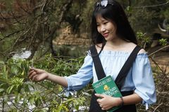 Woman Wearing Blue Off-shoulder Blouse Holding Book Next to Green Leaf Plant Royalty Free Stock Photos