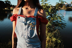 Woman Wearing Blue Overalls and Red Top by a Lake Royalty Free Stock Photo