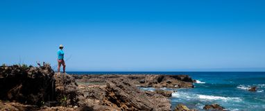 Woman stands on rocks overlooking the Pacific Ocean royalty free stock photo