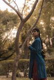 Woman Wearing Blue and Red Dress Standing Beside Tree stock photo