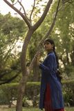 Woman Wearing Blue and Red Long-sleeved Dress Near Tree royalty free stock image