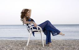 Woman Wearing Blue Two-piece Dress Sitting on White Armchair Near Beach Stock Photography
