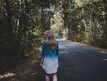 Woman Wearing Blue and White Long-sleeved Shirt Walking Near Tree Royalty Free Stock Photo