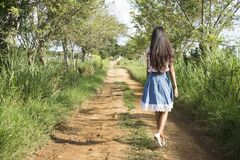 Woman Wearing Blue and White Skirt Walking Near Green Grass during Daytime Royalty Free Stock Photography