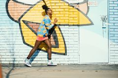 Woman Wearing Blue and Yellow Long-sleeved Shirt Walking Near White and Yellow Painted Wall Royalty Free Stock Image