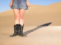 Woman Wearing Boots and Short Skirt. Woman wearing cowboy boots and short denim skirt standing in desert sand. Horizontal shot stock photography