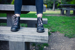 Woman wearing boots sitting on bench Stock Image