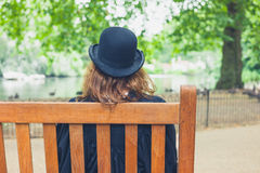Woman wearing bowler hat in park on bench Stock Photography