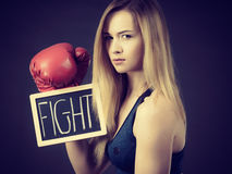 Woman wearing boxing glove holding fight sign. Young sporty woman wearing boxing glove holding black board with fight text sign. Studio shot on black background royalty free stock photo