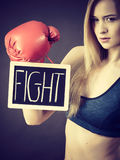 Woman wearing boxing glove holding fight sign. Young sporty woman wearing boxing glove holding black board with fight text sign. Studio shot on black background stock photos