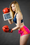 Woman wearing boxing glove holding fight sign. Young sporty woman wearing boxing glove holding black board with fight text sign. Studio shot on black background royalty free stock images