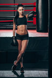 Woman wearing boxing gloves near punching bag Stock Images