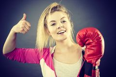 Woman wearing boxing gloves showing thumb up. Sporty happy woman wearing red boxing gloves showing positive gesutre thumb up. Studio shot on dark background stock photography