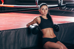 Woman wearing boxing gloves sitting near ring Stock Images