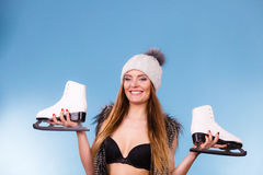 Woman wearing bra and holding ice skates Stock Photography