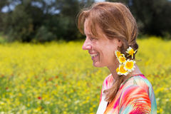 Woman wearing braid with yellow flowers near coleseed field. Laughing caucasian woman wearing braid with yellow flowers near rapeseed field royalty free stock photos