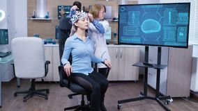 Woman wearing brainwave scanning headset sitting on a chair