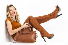 Woman wearing brown clothes. Sitting woman wearing brown clothes and boots with a handbag Stock Images