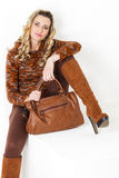 Woman wearing brown clothes. Sitting woman wearing brown clothes and boots with a handbag Stock Photo