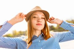Woman Wearing Brown Hat and Blue Striped Dress Shirt stock image