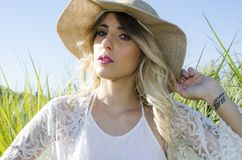 Woman Wearing Brown Hat and White Cardigan Standing in Middle of Grass Field Stock Photos