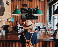 Woman Wearing Brown Hut and Brown Backpack Facing Brown Wooden Table Royalty Free Stock Image