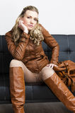 Woman wearing brown jacket. And boots sitting on sofa Royalty Free Stock Image