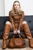 Woman wearing brown jacket. And boots sitting on sofa Stock Images