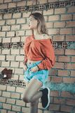 Woman Wearing Brown Long-sleeved Blouse and Blue Denim Short Shorts Standing Behind Brown Brick Wall Royalty Free Stock Images