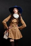 Woman wearing brown overcoat and cap blue. Expressive fashion studio shot of young and beautiful woman wearing brown overcoat on dark background. (Professional Royalty Free Stock Photos