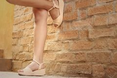 Woman wearing brown shoes standing on a cement floor. Royalty Free Stock Photography