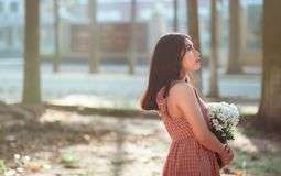 Woman Wearing Brown Sleeveless Dress Carrying White Flower Bouquet Stock Photo