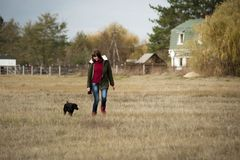 Woman Wearing Brown Zip-up Jacket and Blue Denim Jeans Walking Beside Short-coated Black Dog at Daytime Royalty Free Stock Images