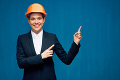 Woman wearing building helmet pointing finger at copy space Stock Photos