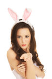 Woman wearing bunny ears and blowing a kiss Stock Images