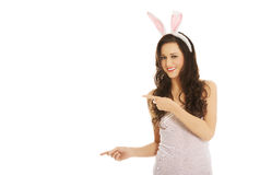 Woman wearing bunny ears and showing copyspace Stock Photo