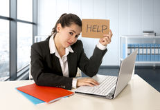 Woman wearing a business suit working on her laptop holding a help sign sitting at modern office royalty free stock photos