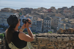 Woman wearing cap making video. Back view on long haired woman wearing cap making video on camera at summertime. A town in background Stock Image