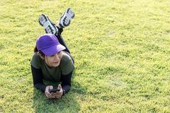 Woman wearing a cap, resting on a lawn. stock image