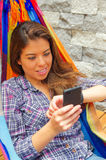 Woman wearing casual clothes holding mobile phone lying in hammock smiling, raising arm looking at smart watch, grey Royalty Free Stock Image
