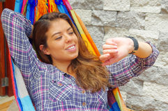 Woman wearing casual clothes lying in hammock smiling, raising arm looking at smart watch, grey brick wall background Stock Photo