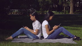 Woman wearing in casual top and jeans use application on cell. Happy friends sitting on the lawn with green grass using mobile phone. Two young asian women stock video