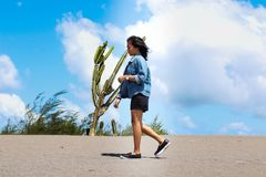 Woman Wearing Chambray Jacket and Black Shorts Walking on Sand Near a Cactus at Daytime royalty free stock image