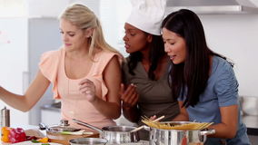 Woman wearing a chef hat and smelling a meal with friends