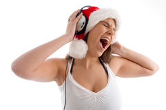 Woman wearing christmas hat and enjoying music Royalty Free Stock Image