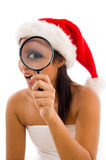 Woman  wearing christmas hat and holding magnifier Royalty Free Stock Photography