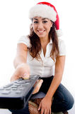 Woman wearing christmas hat and showing remote Royalty Free Stock Photos