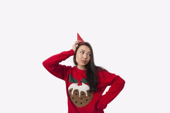 Woman wearing Christmas jumper and party hat against gray background Royalty Free Stock Photography