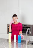 Woman wearing cleaning gloves standing in a kitchen Royalty Free Stock Photos